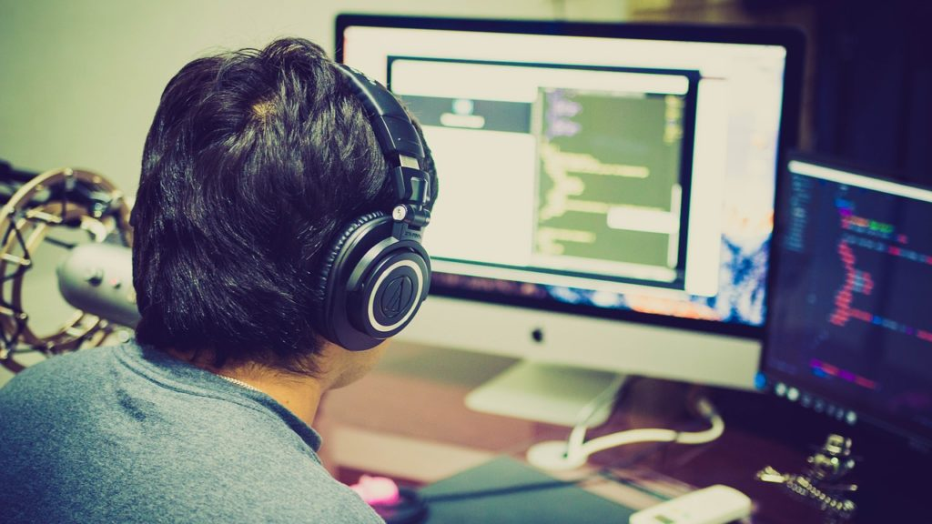 programista w słuchawkach koduje